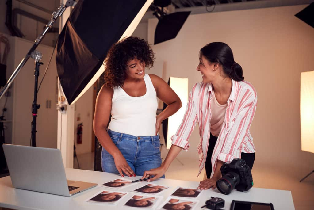 laughing photographer reviews headshots with smiling curly haired model in all white studio.