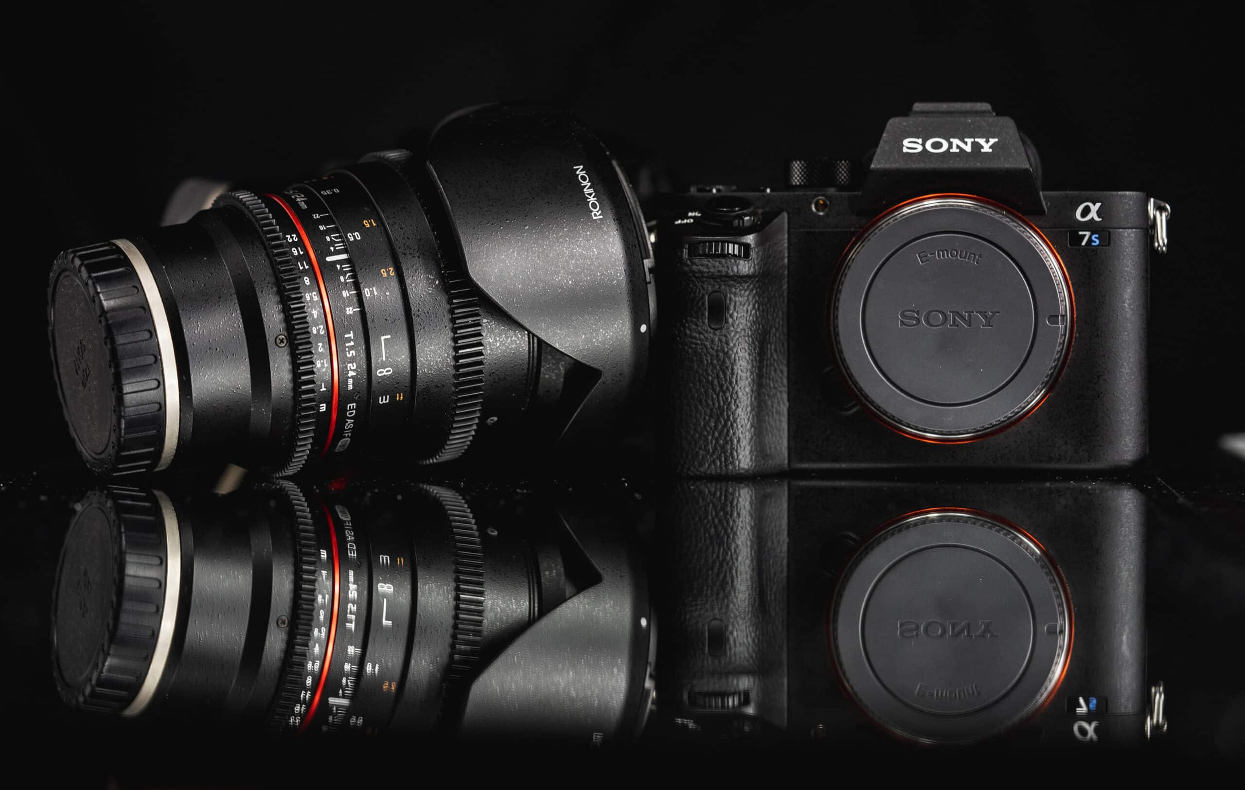 Sony a7ii and Rokinon 24mm lens displayed on reflective surface
